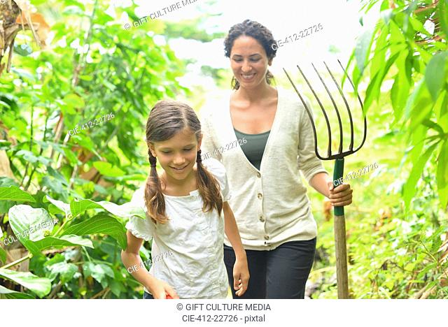 Girl and woman with gardening fork walking through plants in greenhouse