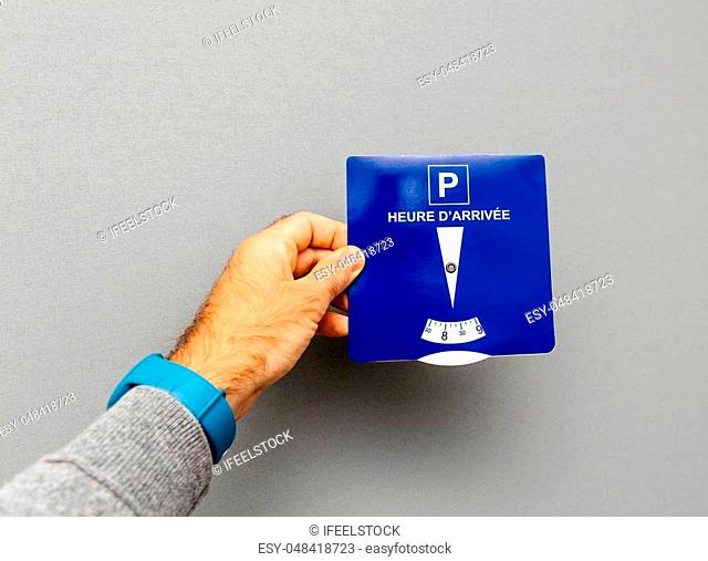 Point of view of man holding disk parking with french text Heure d'arrivee translated as Arrival time from French language - gray background