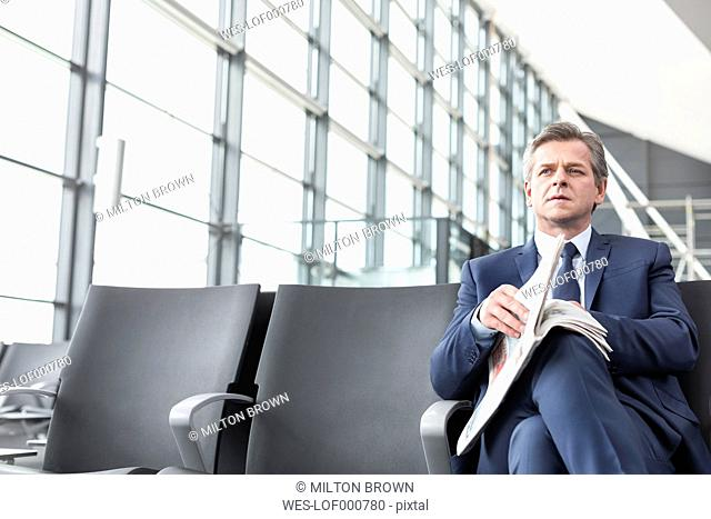 Businessman with newspaper at airport departure lounge