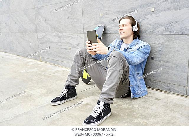 Young man with skateboard sitting on ground, using digital tablet