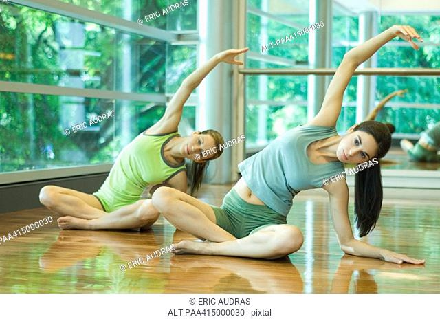 Exercise class, women doing side stretch