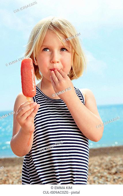 Child with fingers on lip holding ice lolly