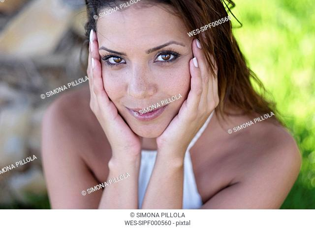 Portrait of smiling brunette young woman outdoors