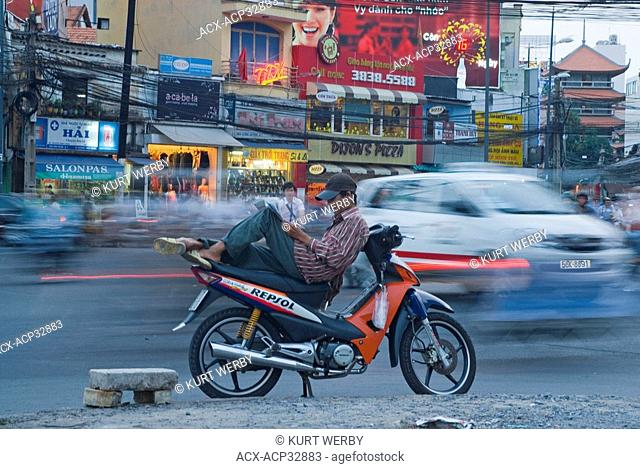 Taking a reading break on the busy streets of Ho Chi Minh City Saigon, Vietnam