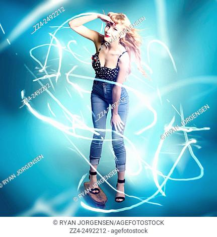 Abstract portrait of beautiful teen girl standing in full length on skateboard over a movement of abstract light trails. Electric blue skater pinup