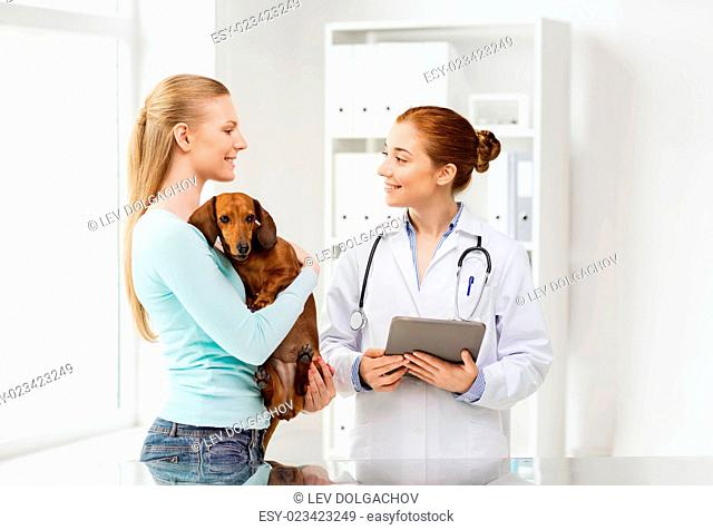 medicine, pet, health care, technology and people concept - happy woman holding dachshund dog and veterinarian doctor with tablet pc computer talking at vet...