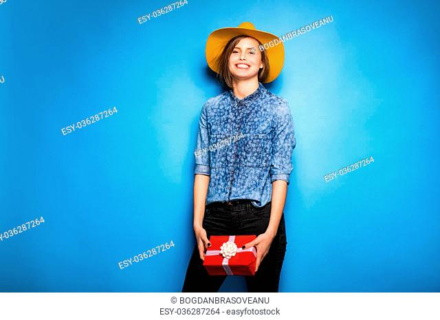 young modern woman holding a red gift in hands, on blue background