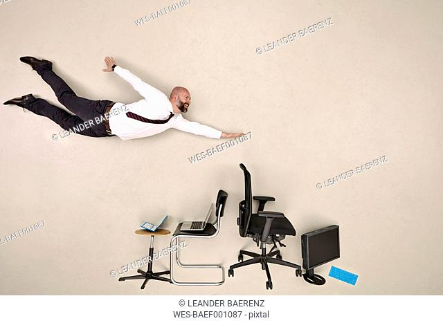 Businessman flying over chairs and devices