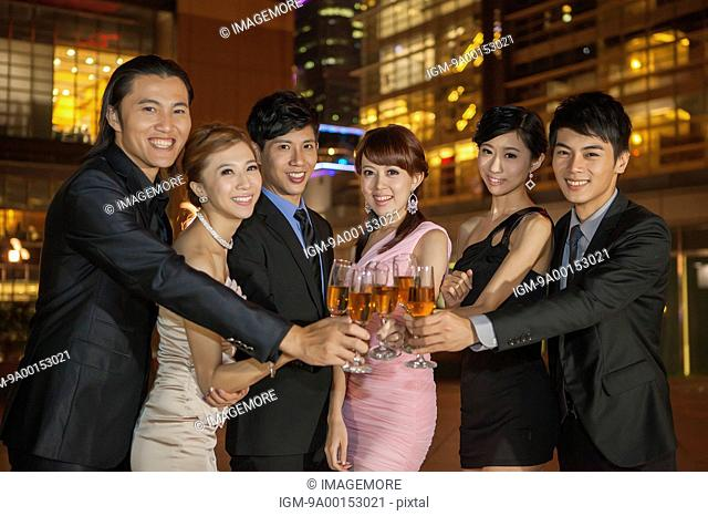 Friends standing in a row and celebrating with wineglass together