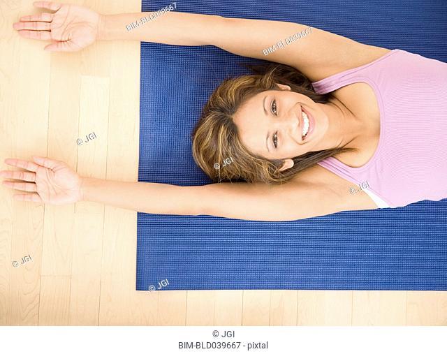 Indian woman laying on yoga mat
