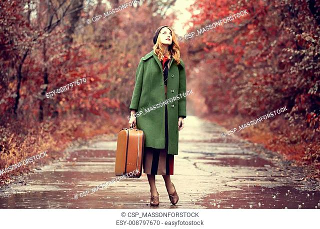 Style redhead girl with suitcase at beautiful autumn alley