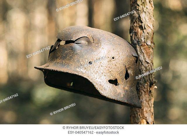 Damaged By Bullets And Shrapnel Metal Helmet Of German Infantry Wehrmacht Soldier At World War II. Rusty Helmet Hanging On Tree Trunk