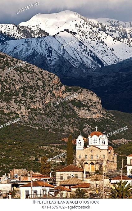 The dramatic, snow covered mountains of the Taygetos range loom over the Outer Mani village of Kambos, Southern Peloponnese, Greece