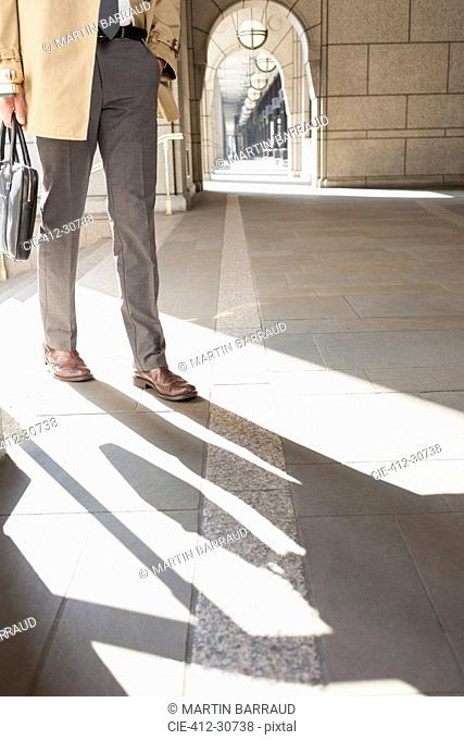 Corporate businessman walking in sunny cloister
