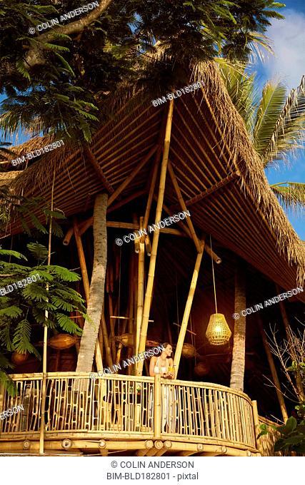 Pacific Islander woman standing on wooden balcony
