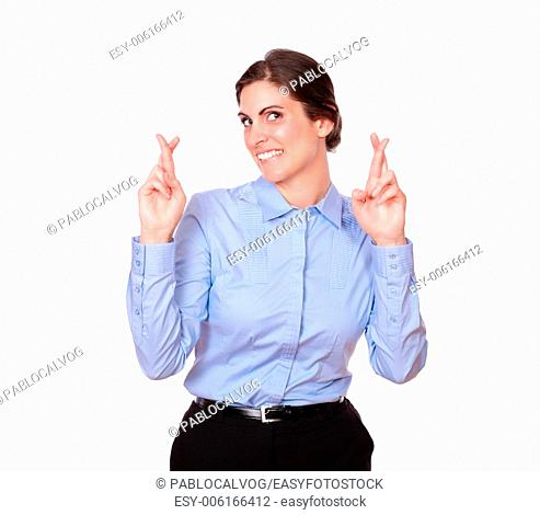 A portrait of a charming gorgeous woman crossing her fingers while standing and smiling at you on isolated studio