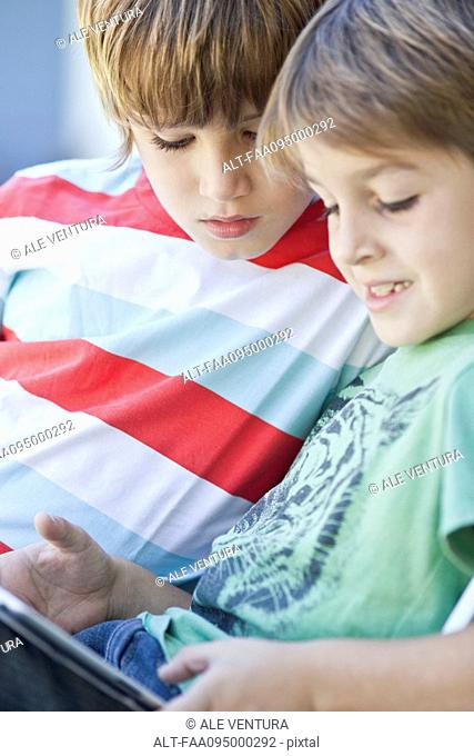 Boys using digital tablet