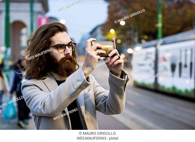 Stylish young man in the city taking a selfie