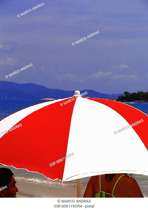 people getting protection under a parasol