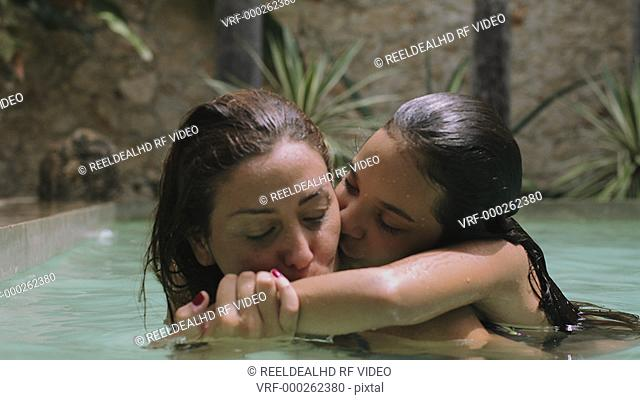 Daughter embracing and kissing to her mother in swimming pool