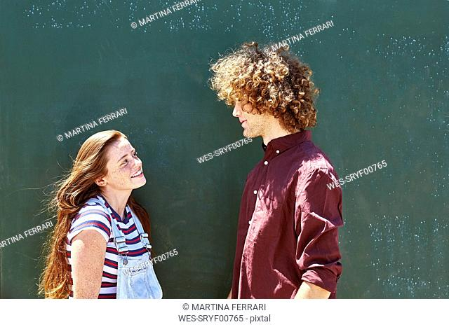 Smiling young couple in front of a green wall