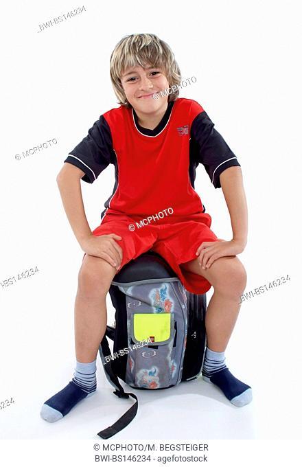 schoolboy sitting on schoolbag