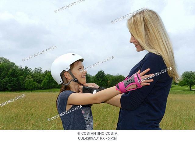 Mother fastening daughter's rollerblading helmet in park