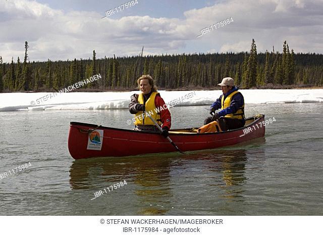 Canoing on Takhini River, snow on shore, Yukon Territory, Canada, North America