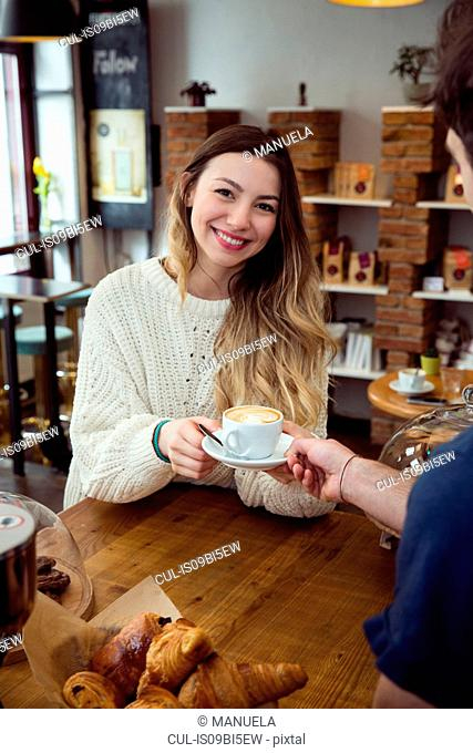 Young woman taking cup of coffee from waiter