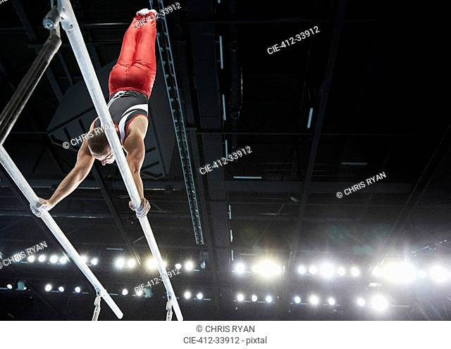 Male gymnast performing upside-down handstand on parallel bars in arena
