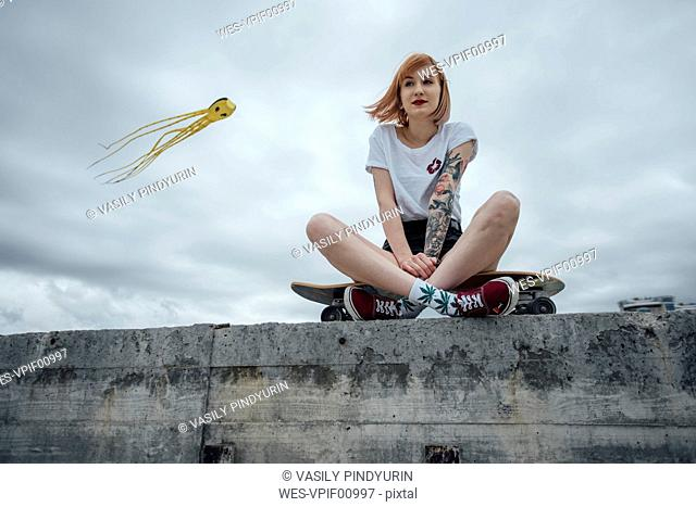 Young woman sitting on a concrete wall on carver skateboard with kite in background