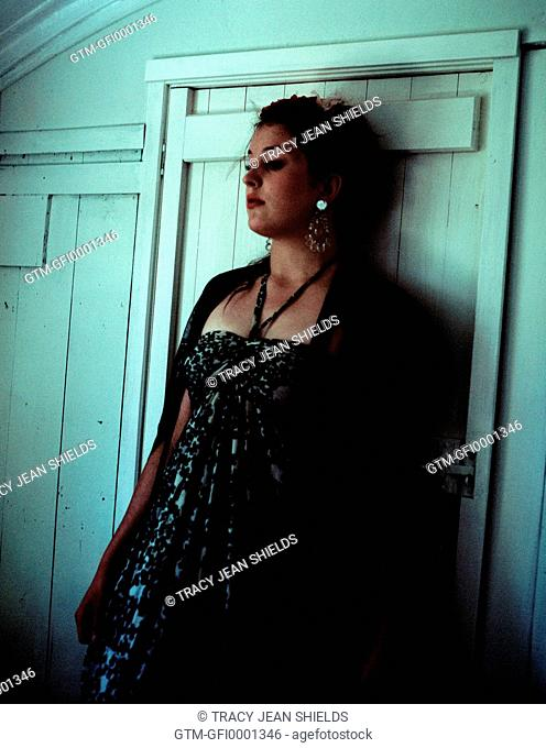 Young woman leaning up against door