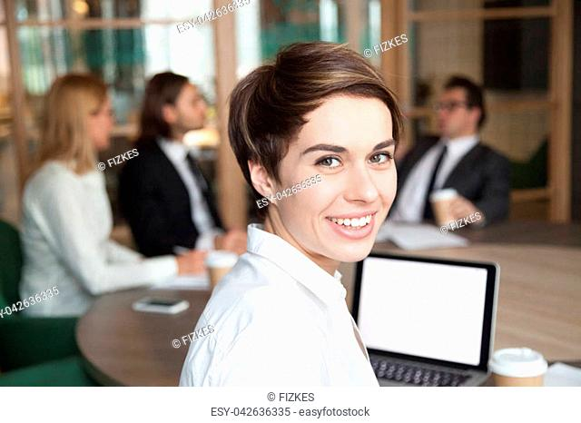 Ambitious attractive smiling young businesswoman looking at camera at group meeting, happy executive manager, team leader