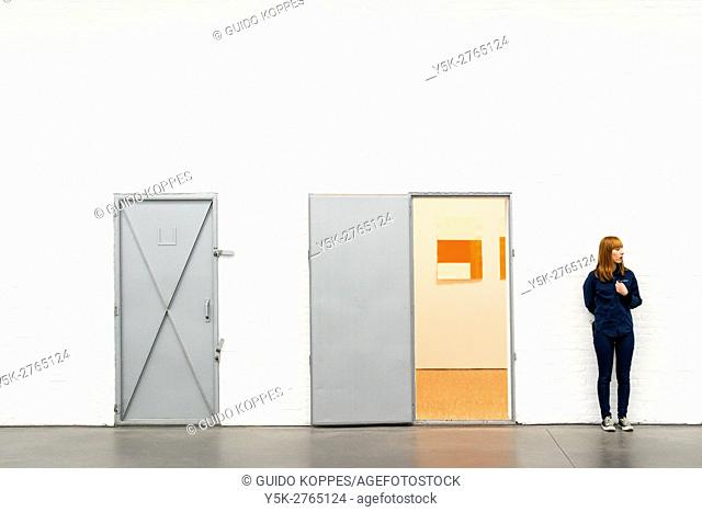 Tilburg, Netherlands. Female turnkey and doorkeeper overseeing visitors at De Pont, the cities local Museum of Modern Art