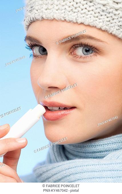 Beautiful woman applying lip balm