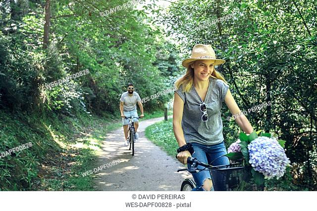 Couple riding bicycle in a forest
