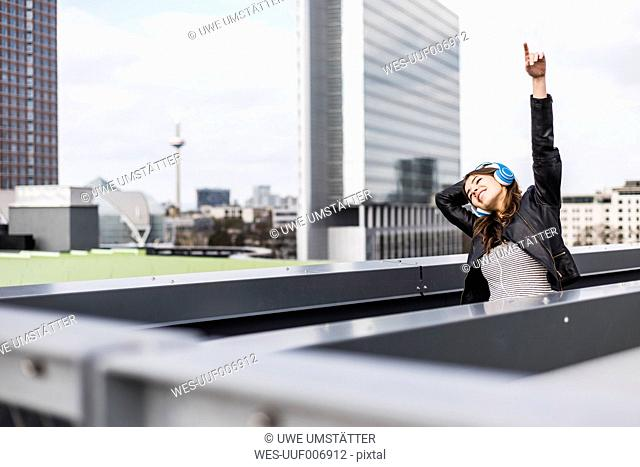 Young woman in the city wearing headphones, dancing