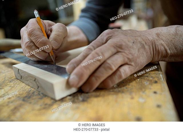 Close up carpenter measuring and marking wood piece