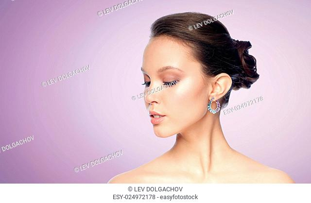 beauty, jewelry, accessories, people and luxury concept - close up of beautiful asian woman face with earring over violet background
