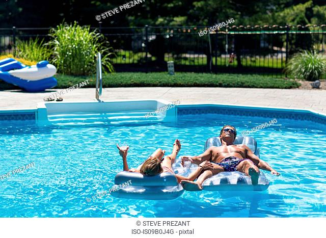 Mature couple in swimming pool, relaxing on inflatables