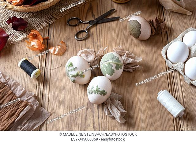Preparation of Easter eggs for dying with onion peels with a pattern of herbs and flowers