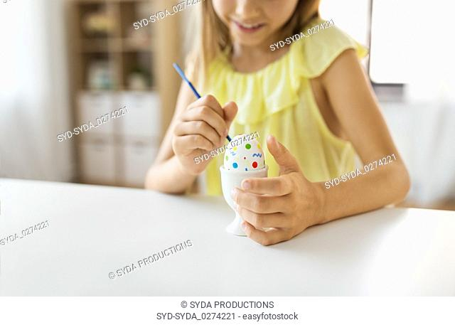 close up of girl coloring easter egg by paintbrush