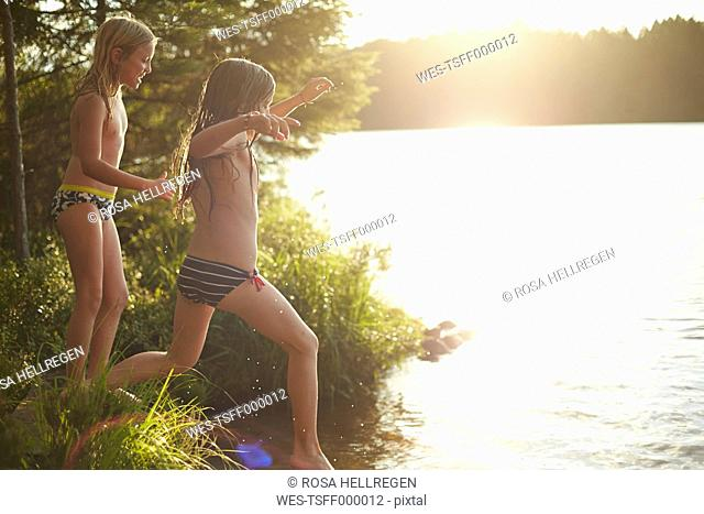 Sweden, two girls jumping into the lake