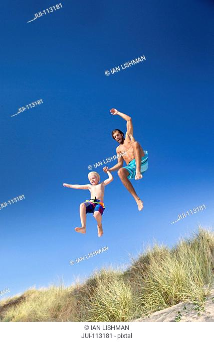 Father and son jumping for joy over sand dune beach grass