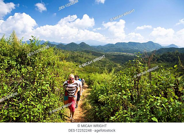 Hiking on a trail through lush foliage with a mountainous landscape in the distance; Hintang, Laos