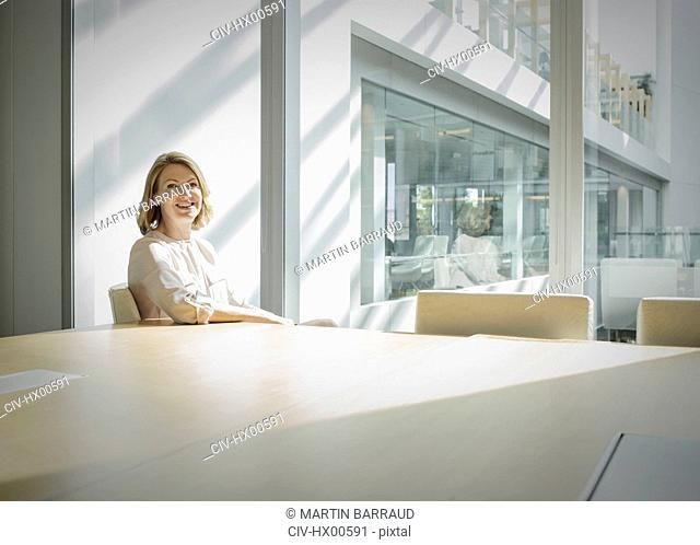 Portrait smiling businesswoman in sunny conference room