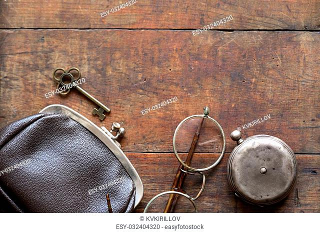 Old spectacles near pocket watch and wallet on wooden background