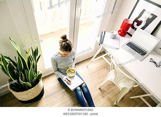 Woman sitting on floor writing on notepad