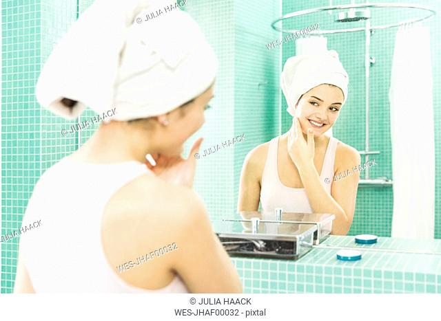 Young woman applying facial moisturizer at mirror in bathroom