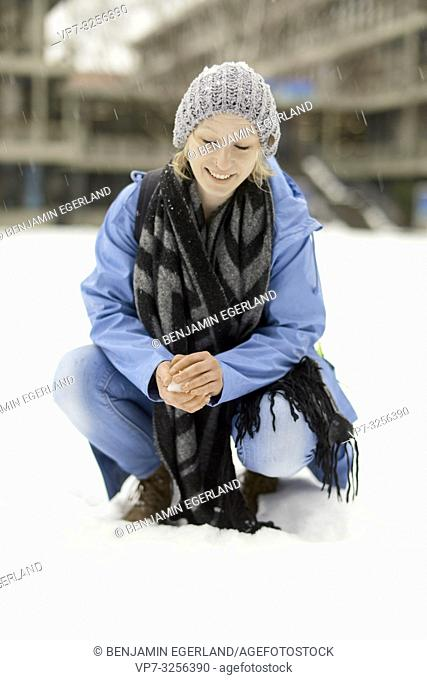 woman crouching on snow in winter, in Munich, Germany